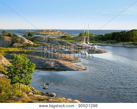 Sailboats Moored At Small Rocky Island