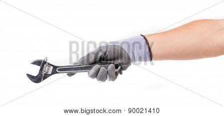 Hand in gloves holding wrench.