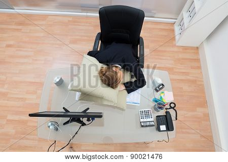 Businesswoman Sleeping On Pillow In Office
