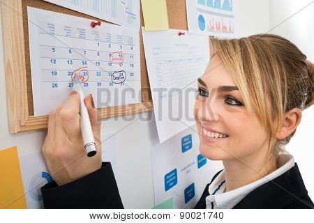 Businesswoman Marking Birthday On Calendar