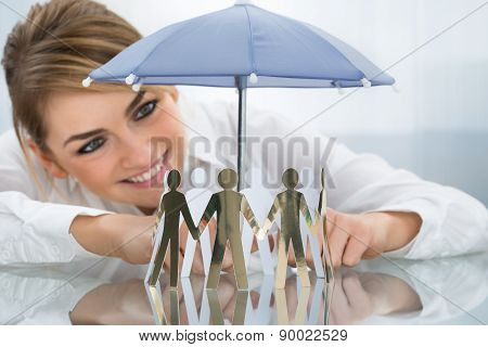 Businesswoman Protecting Cut-out Figures With Umbrella