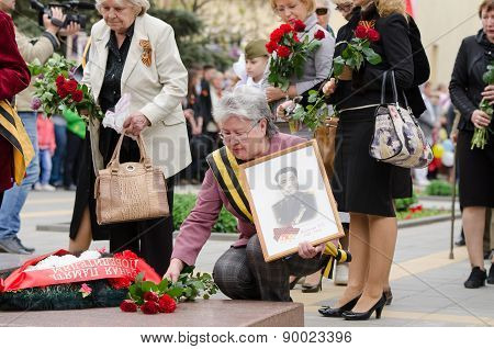 Elderly Woman With A Photo War Lays Flowers At The Monument