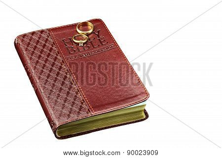 Bible With Wedding Rings Isolated On White