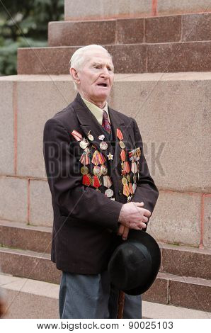 Portrait Of A Veteran On  Background Monument To Fallen