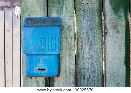Blue Mailbox On Green Fence