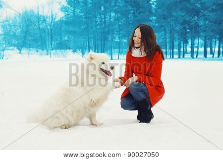Happy Woman Owner Having Fun With White Samoyed Dog Outdoors In Winter Park
