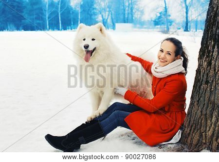 Happy Woman Owner Having Fun With White Samoyed Dog Outdoors On The Snow In Winter Park