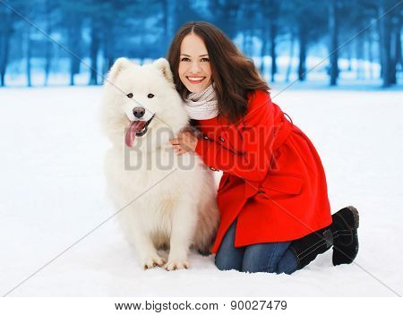 Winter And People Concept - Happy Woman Having Fun With White Samoyed Dog Outdoors In Winter Day