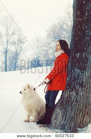 Woman Owner And White Samoyed Dog Near Tree In The Winter Park