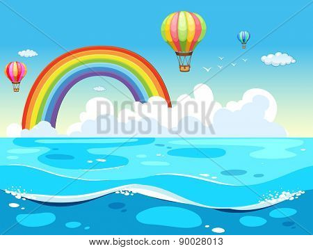 Ocean view with balloons and rainbow in the background