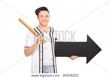 Young man in a baseball shirt holding a baseball bat and an arrow pointing right isolated on white background