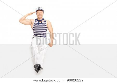 Young male sailor saluting towards the camera seated on a blank white signboard isolated on white background