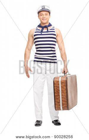 Full length portrait of a handsome young sailor holding a brown bag and looking at the camera isolated on white background