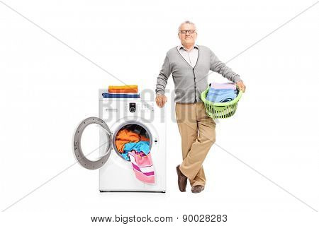 Senior gentleman holding a laundry basket full of clothes and posing next to a white washing machine isolated on white background
