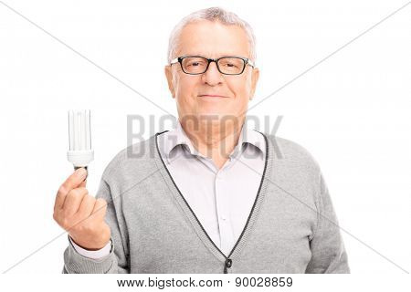 Close-up on a senior gentleman holding an energy efficient light bulb and looking at the camera isolated on white background