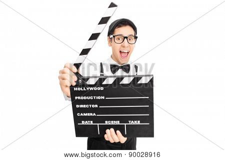 Retro guy posing behind a movie clapperboard and looking at the camera isolated on white background