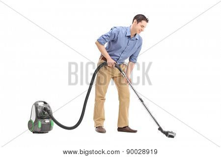 Studio shot of a cheerful young man using a vacuum cleaner isolated on white background