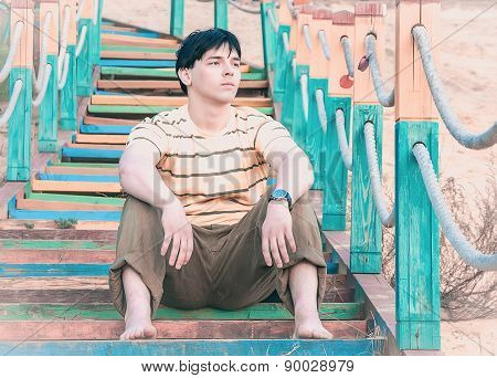 A Young Man Sitting On The Steps