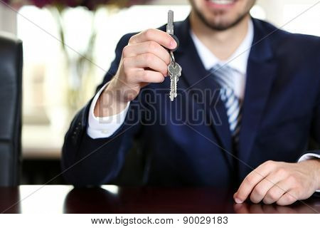 Businessman with keys in his hand in office