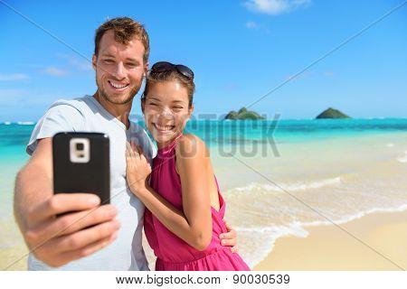 Smartphone - beach vacation couple taking selfie photograph using smartphone having fun holding smart phone camera on Lanikai beach, Oahu Hawaii, USA with Mokulua Islands. Young Asian Caucasian couple