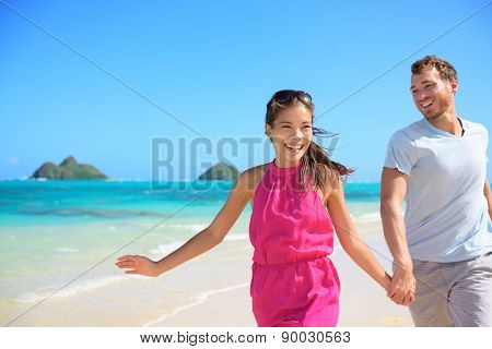 Happy couple on beach running having fun on Hawaii. Romantic couple joyful and full of happiness on travel vacation on Lanikai beach, Oahu, Hawaii, USA with Mokulua Islands. Asian woman, Caucasian man