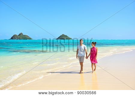 Summer vacation couple walking on beach landscape. Young adults relaxing together enjoying their holidays by pristine turquoise water on Lanikai beach, Oahu, Hawaii, USA with Mokulua Islands.