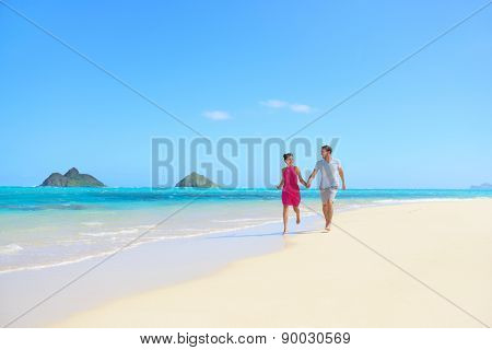 Beach couple happy having fun on Hawaii honeymoon. Romantic couple cheerful and full of happiness on travel vacation, Lanikai beach, Oahu, Hawaii, USA with Mokulua Islands. Asian woman, Caucasian man