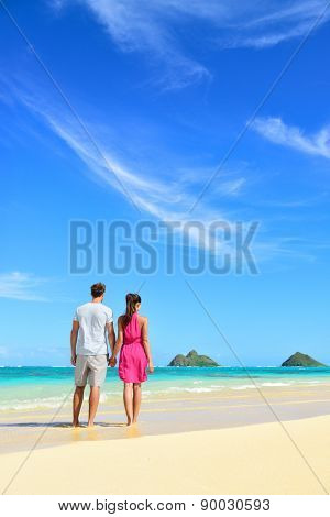 Beach vacation couple relaxing on summer holidays. Young people standing from behind holding hands looking at the ocean on Lanikai beach, Oahu, Hawaii, USA with Na Mokulua Islands.