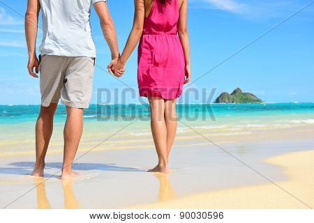 Holding hands romantic newlyweds couple on beach. Closeup of male and female hands with a sunny honeymoon during travel summer holidays on Lanikai beach on Oahu, Hawaii, USA with Na Mokulua Islands