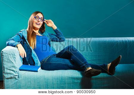 Woman Sitting On Couch Reading Book At Home