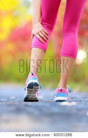 Woman running clutching calf muscle injury after spraining it while out jogging on the beach. Female athlete sport injury. Outside on forest path.