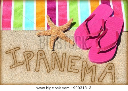 Ipanema beach concept. Overhead view ot the word RIO written on golden sand with a starfish, pink flip flops and towel conceptual of a summer vacation and travel in Rio de Janiero, Brazil
