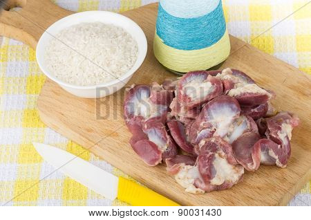 Raw Chicken Gizzards And Hearts, Rice, Oil On Wooden Board