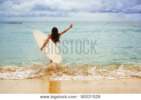 Surfer girl happy cheerful going surfing at ocean beach running into water. Female bikini woman heading for waves with surfboard having fun living healthy active lifestyle by sea.