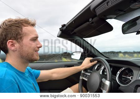 Car driver - young man driving convertible on road trip in summer.