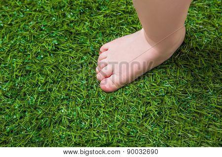 Baby bare leg standing  on green grass