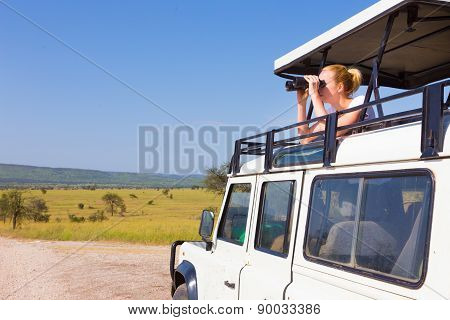 Woman on safari looking through binoculars.