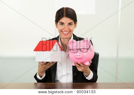 Businesswoman Holding House Model And Piggybank