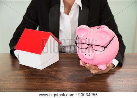 Businesswoman With House And Piggybank