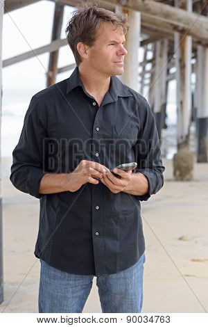 Man Using Smart Phone At Beach