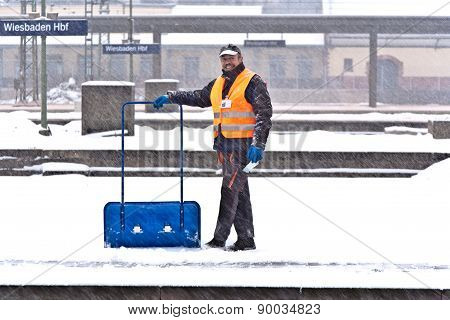 Worker is cleaning the train platform from snow
