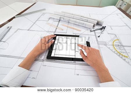 Architect With Digital Tablet Over Blueprint