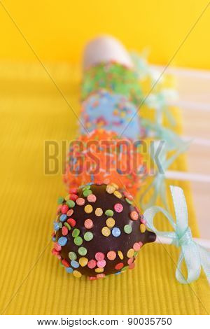 Sweet cake pops on table on yellow background