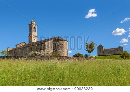 Field with high green grass and old stone church under blue sky in spring in Piedmont, Northern Italy.