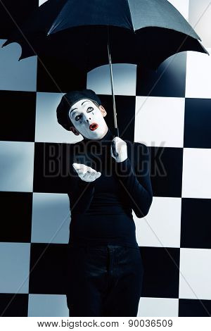 Male mime artist stands under an umbrella in the rain and expressing different emotions. Chess board background.