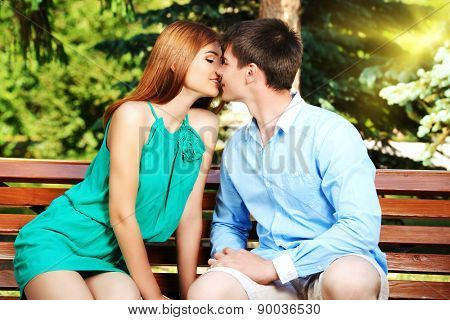 Young people tenderly kissing on a park bench. Love concept.