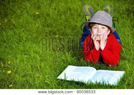 Cute 7 years old boy lying on a grass with a book. Summer day.