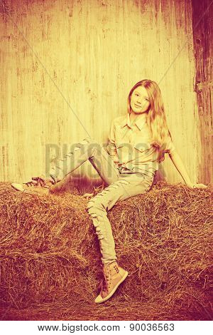 Pretty girl teenager in shirt and torn jeans posing on hay. Jeans fashion. Western style. Sepia.