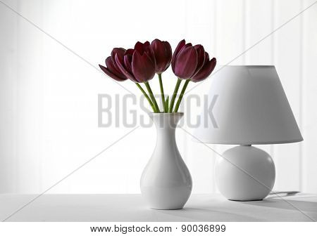 Beautiful violet tulip in vase with lamp on light background