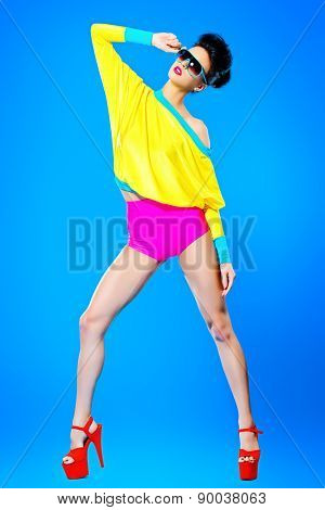 Glamorous fashion model posing in vivid colourful clothes and sunglasses. Bright fashion. Optics, eyewear. Studio shot.